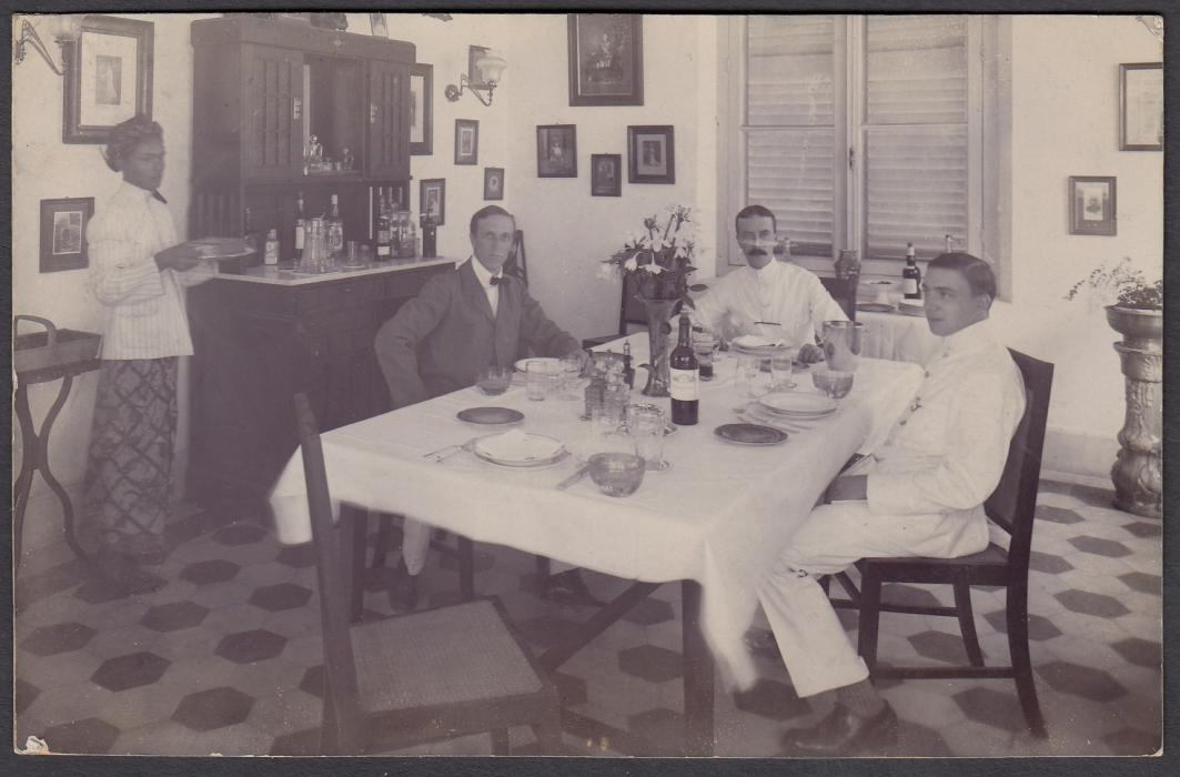 NETHERLANDS INDIES: (Picture Stationery) 1911 5c. card with fine photographic image of colonists seated at table with servant, used from Soerabaja to Bath, England.