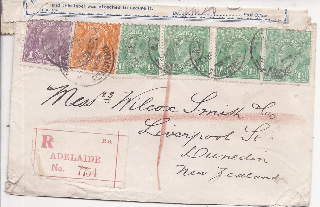 Australia Unclearly dated registered cover to Dunedin, New Zealand franked KGV Heads 1/2d.,1d. and 1 1/2d. (4) tied Adelaide cds, Officially Sealed label applied on arrival as found torn